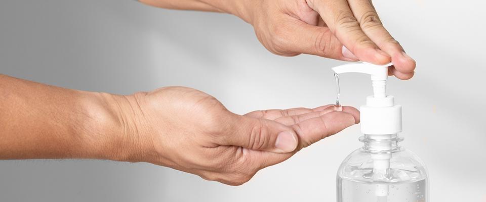 osoba używająca płynu antybakteryjnego podawanego zdozownika